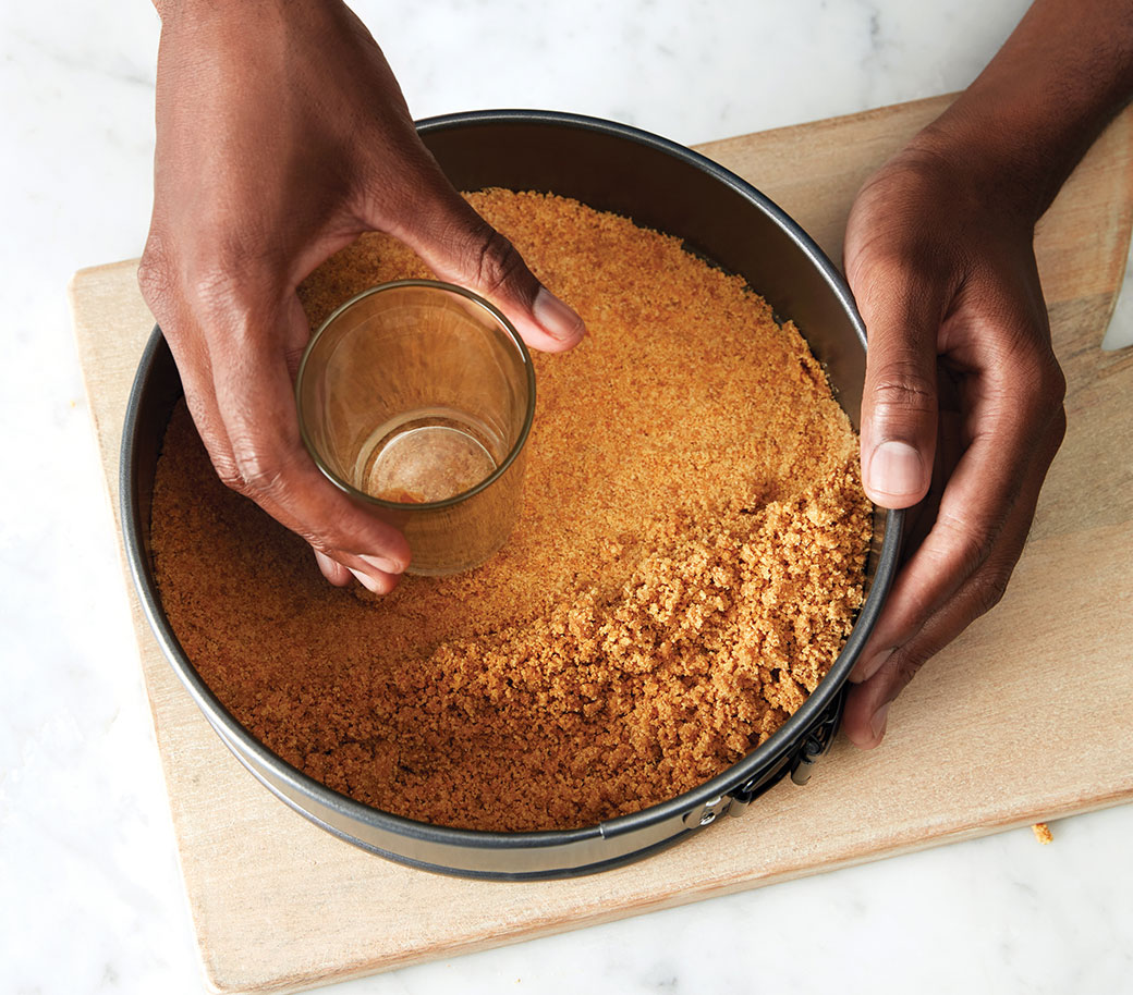 image of hands pressing crumbs into pan using a glass