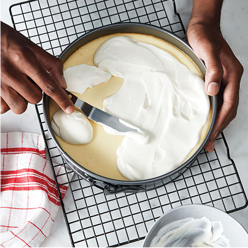 image of topping being spread over baked cheesecake in pan