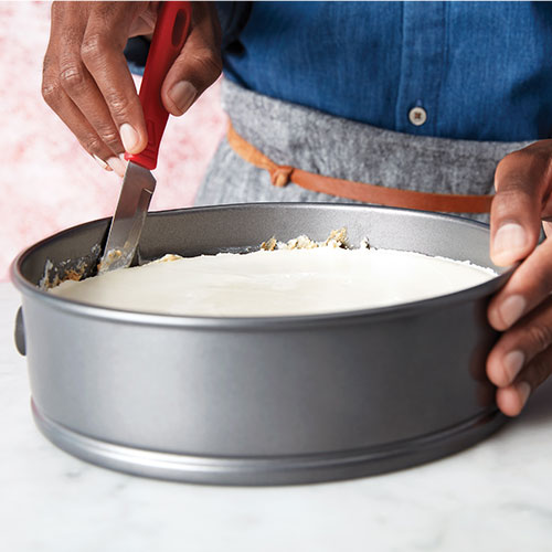 image of hand holding and running a palette knife around edge of cheesecake