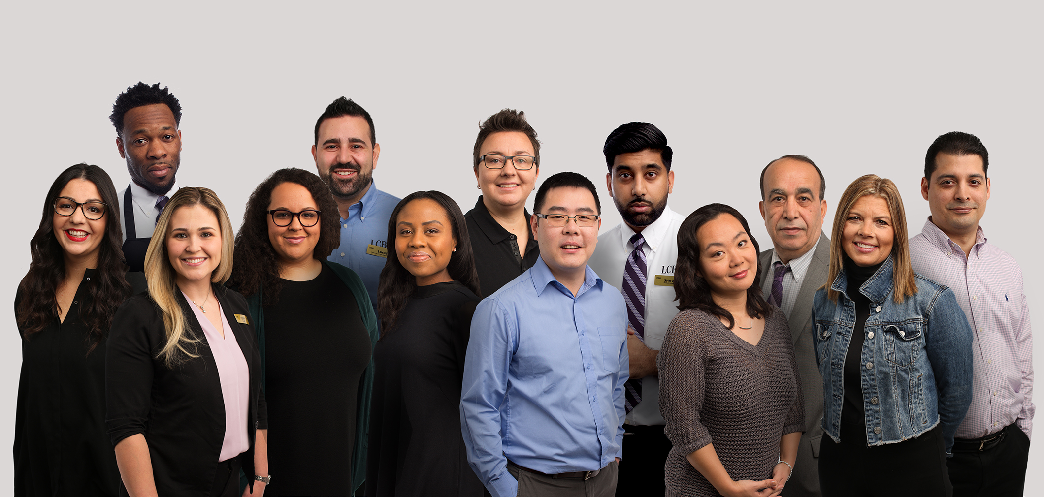Photo of 14 smiling diverse employees from all areas of the business